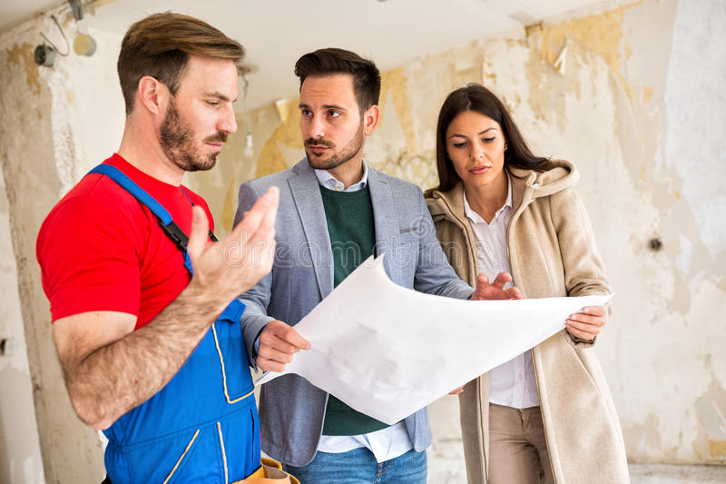 Builder handyman shows to young couple problem iin blueprints of royalty free stock photos