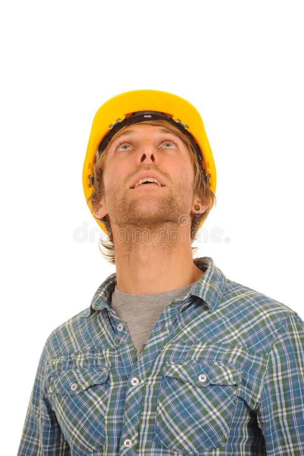 Builder in a hard hat. A young builder or workman wearing a yellow hard hat looks upward stock photos