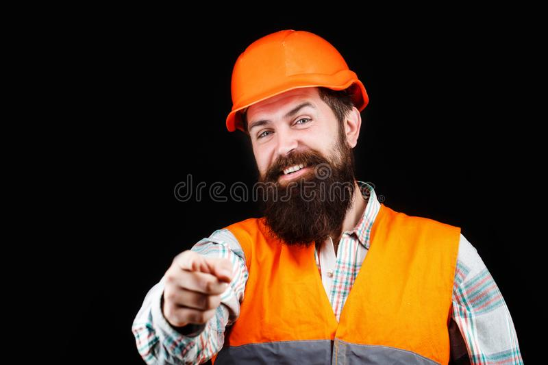 Builder in hard hat, foreman or repairman in the helmet. Portrait of a builder smiling. Bearded man worker with beard in stock photography