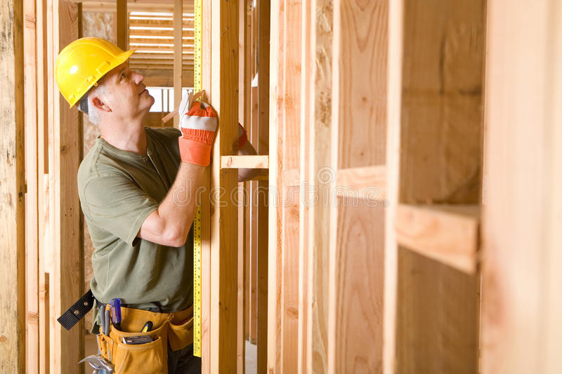 Builder in hardhat measuring beam, side view royalty free stock photo