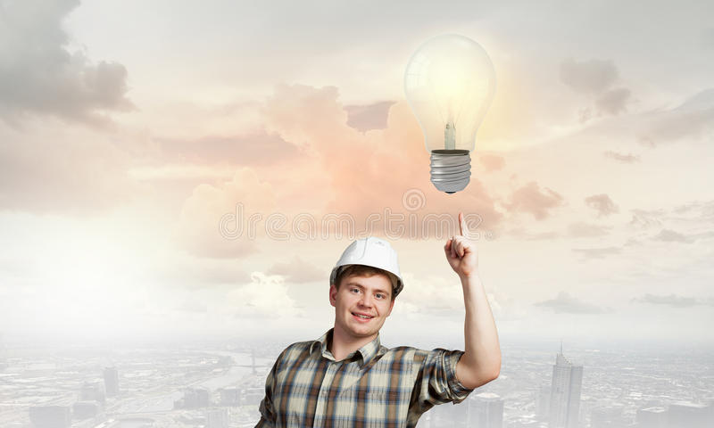 Builder has an idea. Young man builder looking thoughtfully at light bulb. Idea concept stock photo