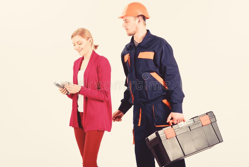 Builder in helmet looks at woman counting money, royalty free stock photo