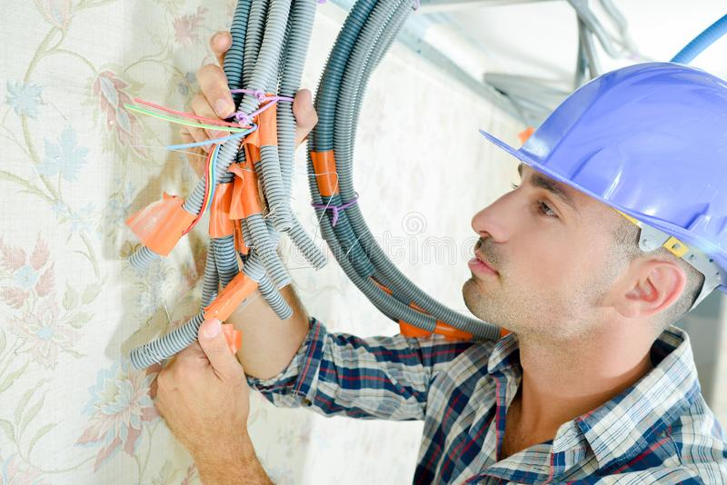Builder holding cables together with tape & ties royalty free stock photos