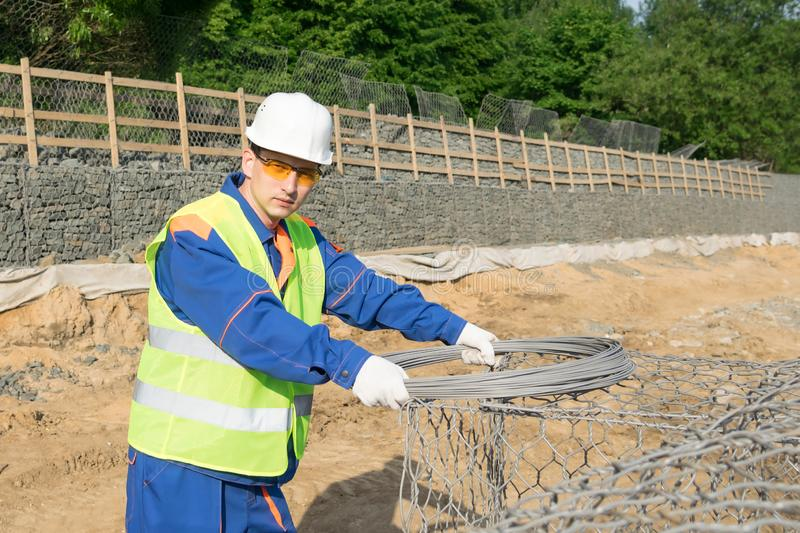 Builder holds a skein of wire and looks into the frame royalty free stock photography