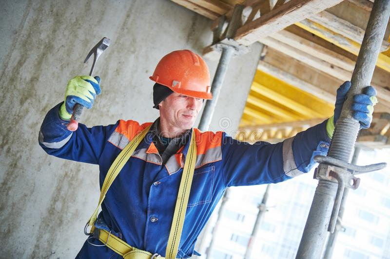 Builder installing or dismantling pole support for concrete monolithic formwork at housebuilding stock image