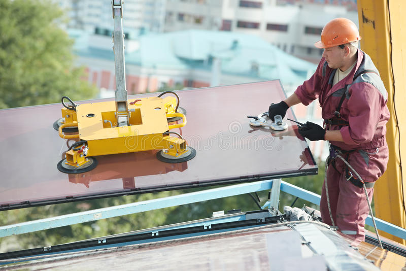 Builder joiner installing glass window on building stock image