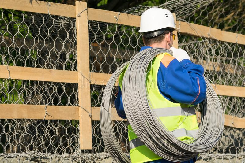 Builder with large skeins of wire for work, rear view stock images