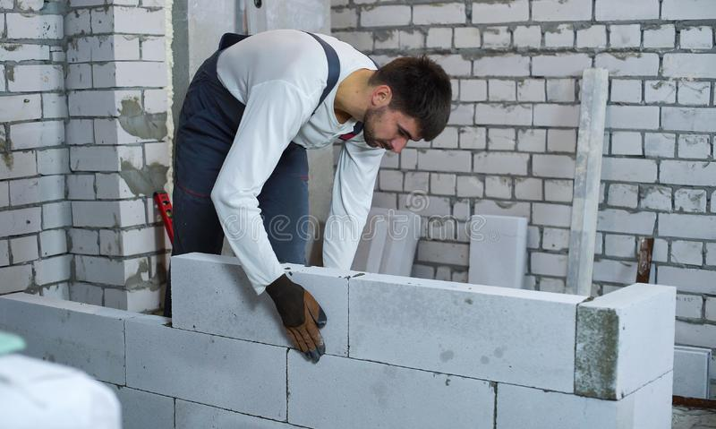 Builder laying aerated concrete blocks at interior construction site. Worker in uniform and gloves building wall. house renovation, construction and manual royalty free stock photo
