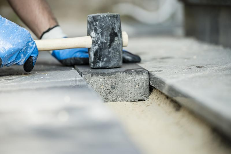 Builder laying a paving stone or brick. Tamping it down with a rubber mallet royalty free stock image