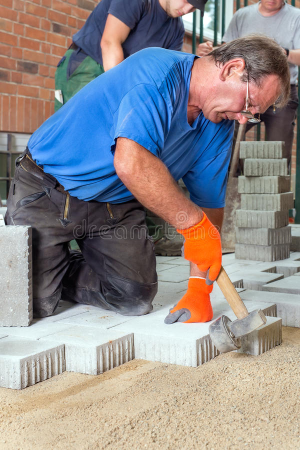 Builder laying paving stones with his team. royalty free stock photography