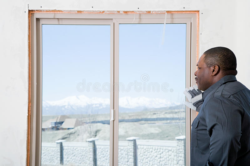 A builder looking out of a patio door stock photo