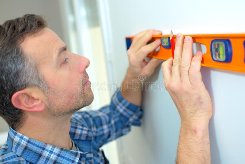 Builder making sure wall straight royalty free stock photography