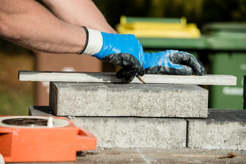 Builder marking a paving stone or block to cut. Builder marking a paving stone or block for cutting as he lays a new floor in a close up view of his gloved hands royalty free stock photography