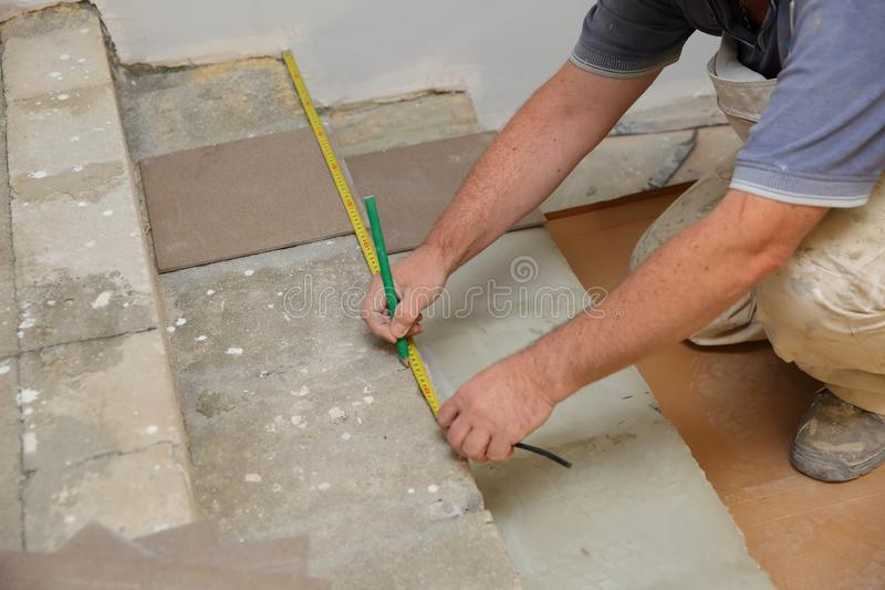 The builder measures the floor with a scoop to arrange the laying of ceramic tiles on the stairs well. Budowlaniec measures and plans to lay ceramic tiles stock photos