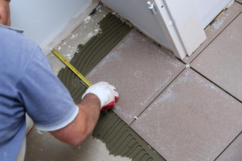 The builder measures the floor with a scoop to arrange the laying of ceramic tiles on the stairs well. Budowlaniec measures and plans to lay ceramic tiles stock photography