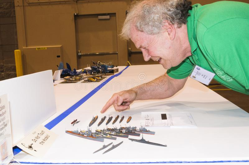The builder of Models of military ships displays at the International Model Convention in Phoenix. Craftsman and builder of miniature model ships arranges the stock photography