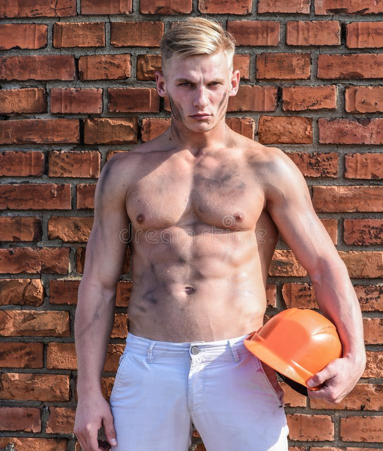 Builder with muscular torso and helmet, brick wall on background. Athlete with nude torso with hard hat relaxing royalty free stock photography