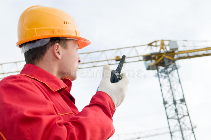 Builder operating the tower crane. Builder worker in uniform and helmet operating with tower crane by portable radio station transmitter royalty free stock photo
