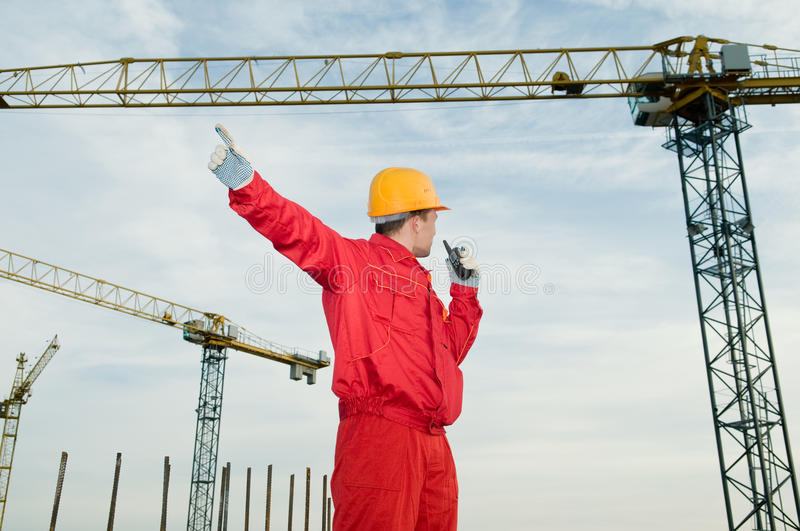 Builder operating the tower crane. Builder worker in uniform and helmet operating with tower crane by portable radio station transmitter royalty free stock images