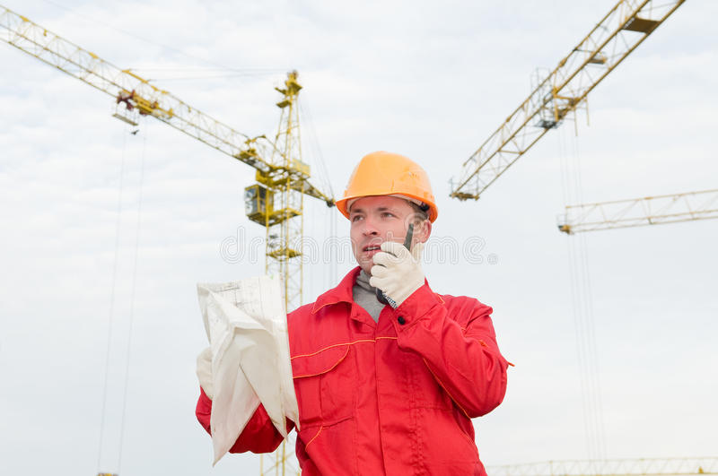 Builder operating the tower crane. Builder worker in uniform and helmet operating with tower crane by portable radio station transmitter royalty free stock photos