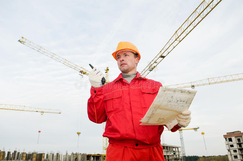 Builder operating the tower crane. Builder worker in uniform and helmet operating with tower crane by portable radio station transmitter royalty free stock image