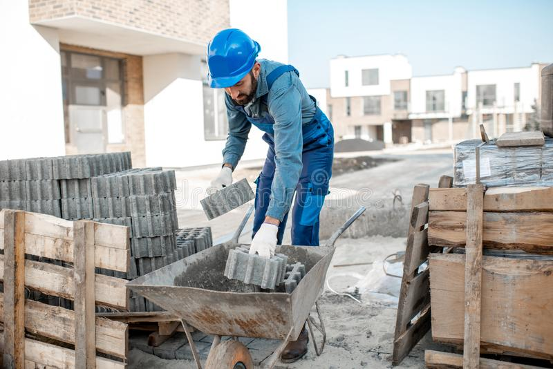 Builder with paving tiles on the construction site royalty free stock photography