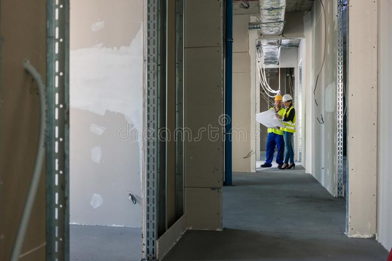 Builder with plan inspecting the construction site stock image