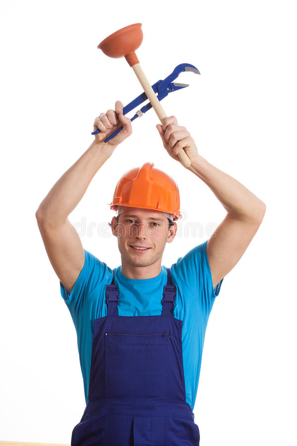 Builder with plunger and wrench. A young builder holding a plunger and an adjustable wrench royalty free stock photography