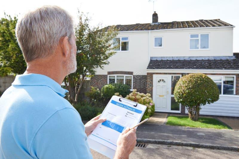 Builder Preparing Estimate For Exterior Home Improvement royalty free stock photo