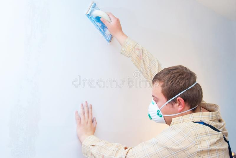 Builder in protect mask polishing the wall stock photography
