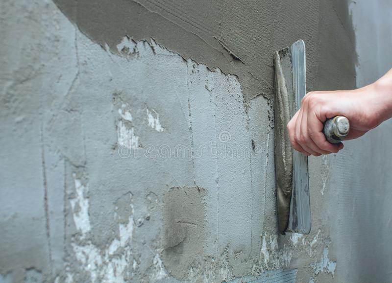 Builder puts mortar trowel wall. Plaster walls. Exterior finish royalty free stock photography