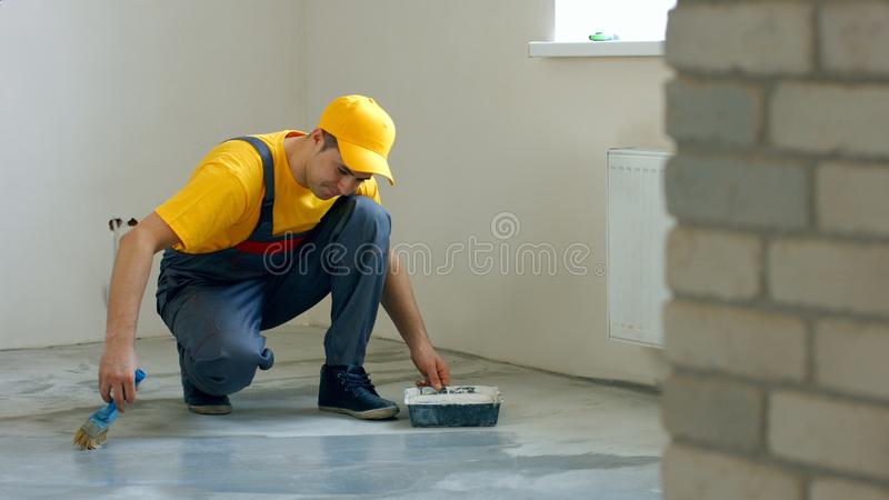 Builder renovating the house. Construction worker processing concrete floor in new apartment. Room floor renovation concept royalty free stock images
