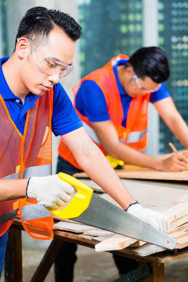 Builder sawing a wood board of building or construction site royalty free stock photography
