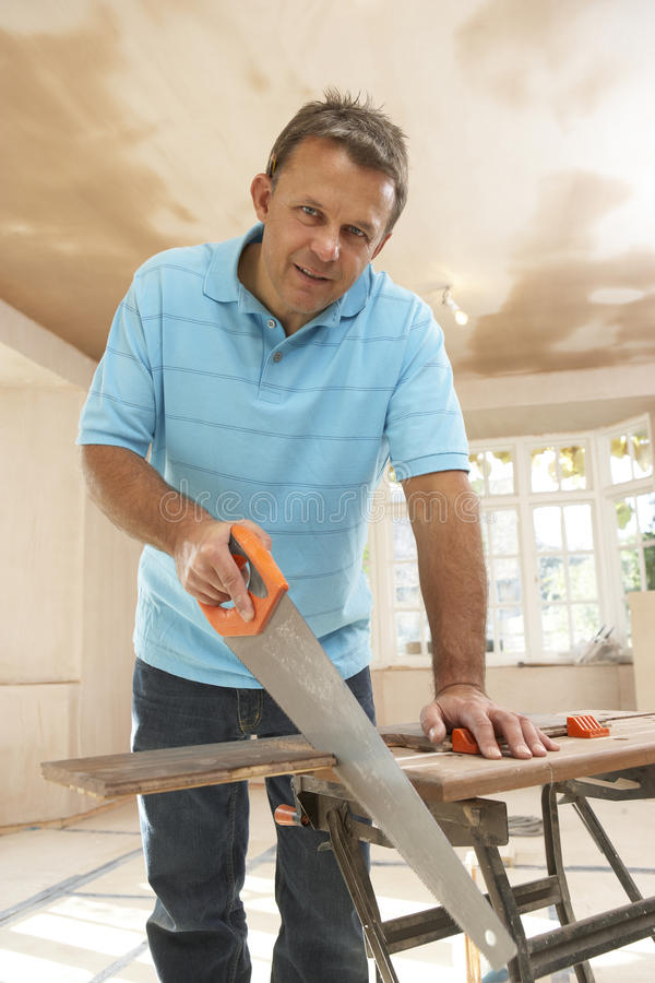 Download Builder Sawing Wood On Workbench Stock Photo - Image: 12407708
