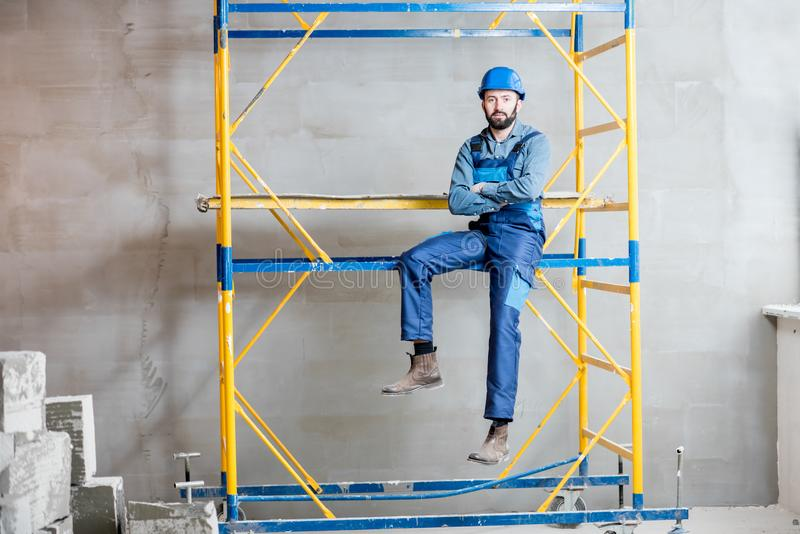 Builder on the scaffolding indoors stock images