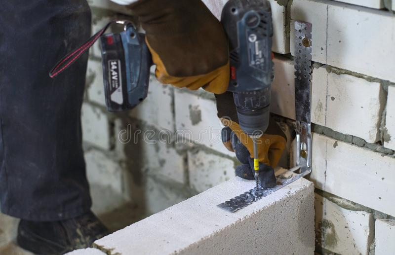 Builder screwing joining clamp in aerated concrete block with electric drill royalty free stock images