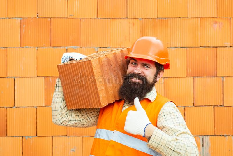 Builder shows thumb up. Labor protection at a construction site. Safety rules for builders. Happy builder in orange royalty free stock image