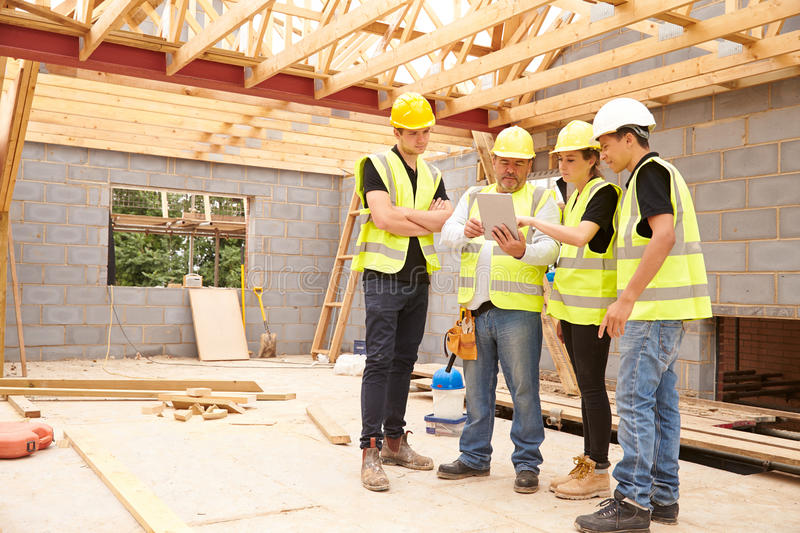 Builder On Site Looking At Digital Tablet With Apprentices stock photography