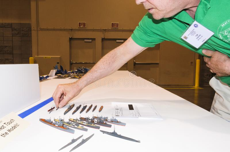 Builder of small ship models displays models at the Modeling Convention in Phoenix, Arizona. The builder of Models of military destroyers arranges the display of stock image