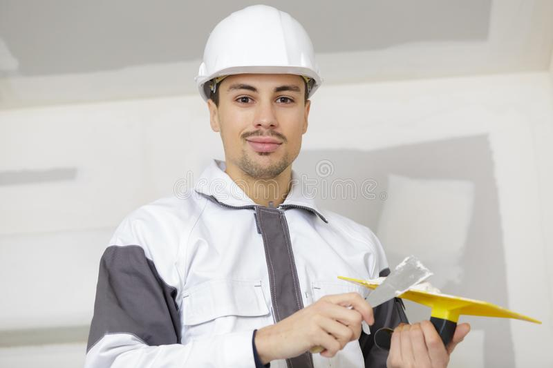 Builder with spatula with plaster in hand royalty free stock photo