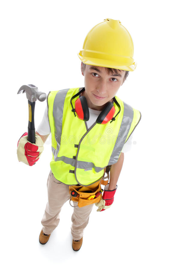 Builder standing with hammer. Above perspective view of a young apprentice builder wearing protective work gear and holding a hammer. White background stock image