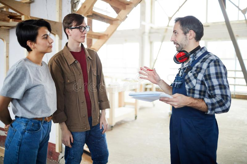 Builder talking to customers. Content confident bearded builder in uniform holding notepad and gesturing hand while talking to young customers at construction stock photography