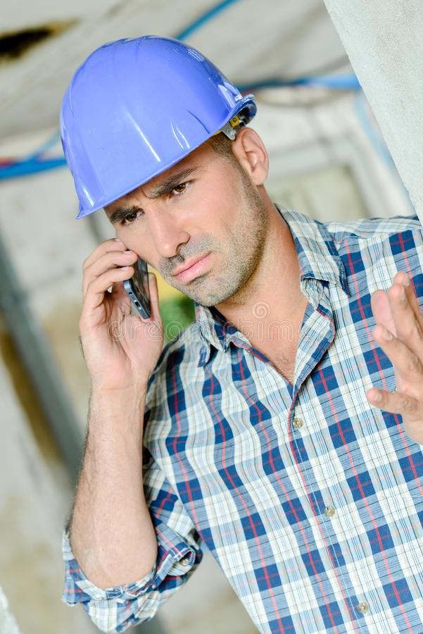 Builder on telephone troubled expression stock images