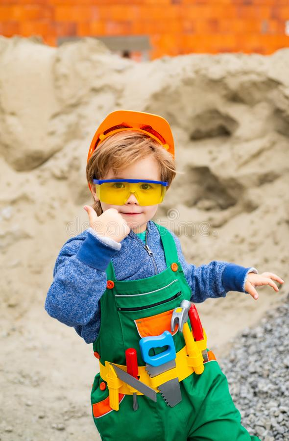 Builder thumb up. The boy is dressed as a builder. Future profession. Career guidance. Happy successful builder. Career stock photography