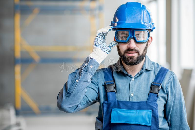 Builder in uniform indoors. Close-up portrait of a handsome bearded builder with protective glasses and helmet indoors royalty free stock images