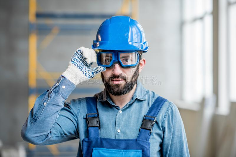 Builder in uniform indoors. Close-up portrait of a handsome bearded builder with protective glasses and helmet indoors stock image