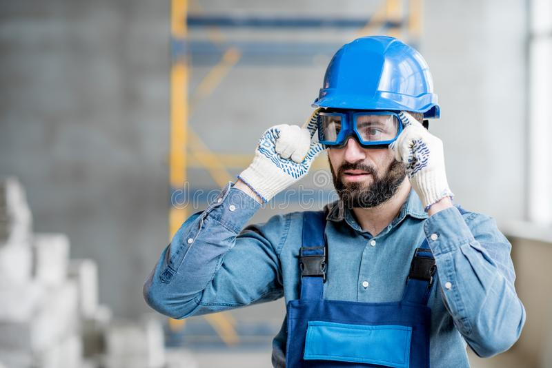 Builder in uniform indoors. Close-up portrait of a handsome bearded builder with protective glasses and helmet indoors royalty free stock photos