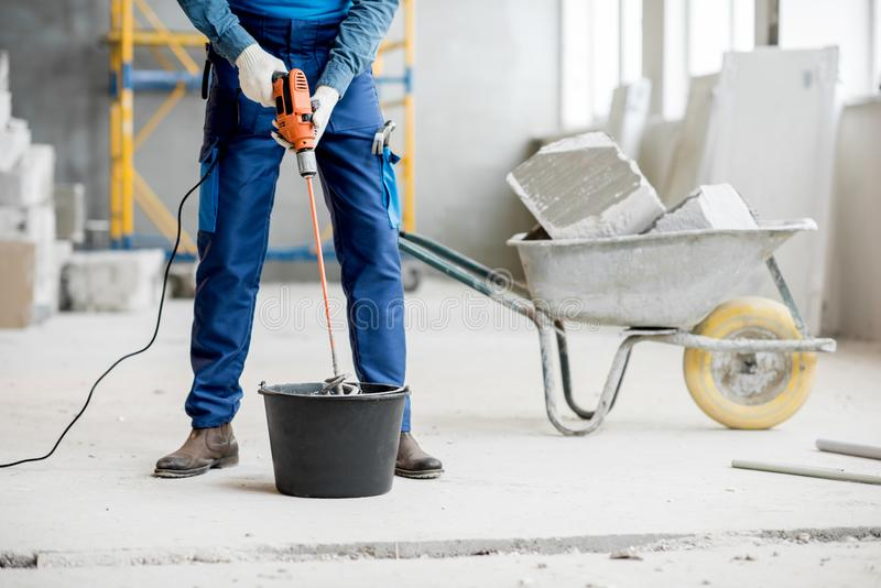 Builder mixing plaster at the construction site royalty free stock images