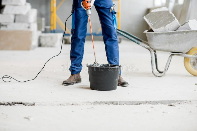 Builder mixing plaster at the construction site royalty free stock image