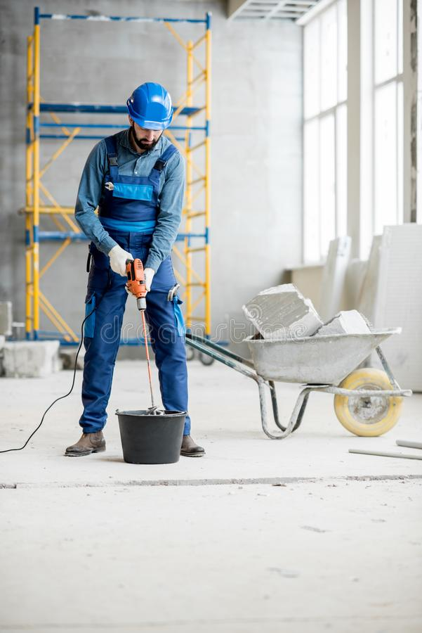 Builder mixing plaster at the construction site royalty free stock photo